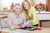 picture of senior-citizen  - Two mature women playing cards - JPG