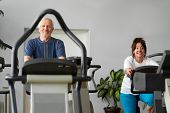 Older Man And Woman Training On A Stationary Bike. Elderly Couple Engaged In Training On A Sports Bi poster