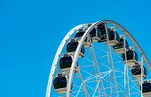 Closeup Modern Ferris Wheel Against Blue Sky And White Clouds. Ferris Wheel At Funfair For Entertain poster