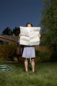 Man in robe reading newspaper in front yard
