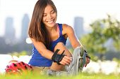 Roller skating woman putting on inline skates for rollerblading. Healthy outdoor workout woman skati