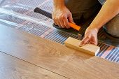 Laminate flooring. Male repairman is laying panel of  laminate floor  on a heat-insulated floor. Ele poster