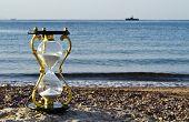 Bronze hourglass on a beach