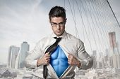 Office worker with glasses opening his shirt like a superhero with the New York skyline in the backg