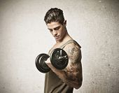 Young man lifting a dumbbell with his left arm, which has a tattoo