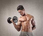 Shirtless young man with the left arm tattooed raising a dumbbell with the right arm