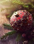 Christmas ball and spruce twigs on wooden background