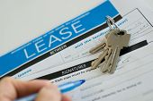 stock photo of rental agreement  - signing a lease with pen and keys - JPG