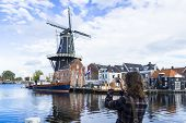 Tourist Girl Is Taking Pictures Of Traditional Dutch Windmill