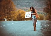 beautiful young girl hitchhiking with poster