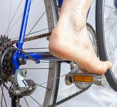 pic of pedal  - Rear view of bare foot on bicycle pedal.