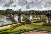 The famous River Kwai bridge in Kanchanaburi under a cloudy sky in rainy season, Thailand