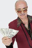 stock photo of hustler  - Portrait of senior man showing US banknotes against gray background - JPG