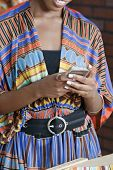 pic of traditional attire  - Midsection of woman in traditional African print attire using cell phone - JPG