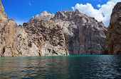 wonderful high rocks both grandiose high-mountainous lake and blue sky with clouds