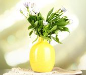 Bouquet of beautiful summer flowers in color vase, on wooden table , on bright background