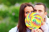 Young surprised couple covering their faces with huge colorful candy