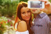 Couple taking self-portrait photos with mobile smart phone