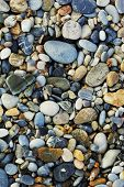 A close up view of smooth polished multicolored stones washed ashore on the beach.
