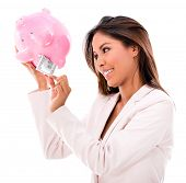 Business woman taking money out from a piggybank - isolated over white