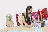 Indian female clothing designer working in design studio