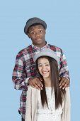 Portrait of happy multi ethnic couple over blue background