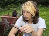 foto of exhale  - A teenage boy sitting in a garden smoking an electronic cigarette and exhaling vapour - JPG