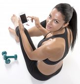 Woman in sport with mobile phone and hand weights
