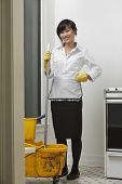 Full length portrait of young maidservant with mop and bucket