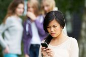 stock photo of bullying  - Teenage Girl Being Bullied By Text Message On Mobile Phone - JPG