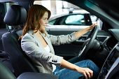Cheerful young woman learning to drive on her own