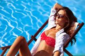 young beautiful  woman in bikini and sunglasses by the pool take sunbath