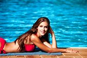 smiling beautiful young woman in bikini by the pool