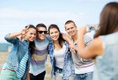summer holidays and technology concept - group of teenagers taking photo outside