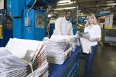 Portrait of a man and woman working in newspaper factory