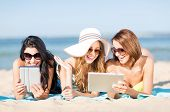 summer holidays, technology and internet concept - girls in bikinis with tablet pc sunbathing on the beach