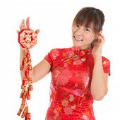 Pretty Asian woman with Chinese traditional dress cheongsam or qipao holding fire crackers. Chinese