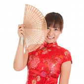 Asian girl with Chinese traditional dress cheongsam or qipao holding Chinese fan. Chinese new year c