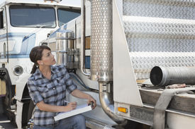foto of logging truck  - Woman inspecting flatbed truck - JPG