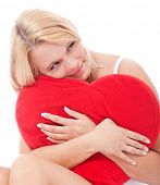 Attractive young woman cuddling heart shaped pillow