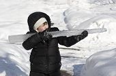 stock photo of gotcha  - Young handsome boy role playing with large icicle in snow - JPG