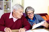 Senior Couple Reading Bills At Home