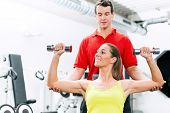 Fitness Paar im Fitnessstudio trainieren mit Gewichten und vergleichen sich