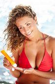 Sunscreen beach woman in bikini applying sun block solar cream for UV protection.