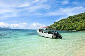 A scuba diving boat is anchored in a beautiful tropical bay of turquoise water and a bright, blue vi