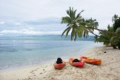 Three orange kayaks sit on a resort beach on an exotic island in Fiji.