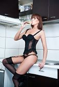 Attractive sexy red hair female with black lingerie and stockings drinking wine in a modern kitchen.