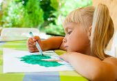 Cute 4 year old girl sitting at table drawing a tree