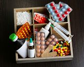 Medical pills, ampules in wooden box, on color wooden background
