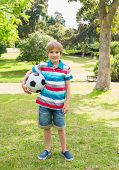 Full length portrait of a smiling young boy with ball at the park